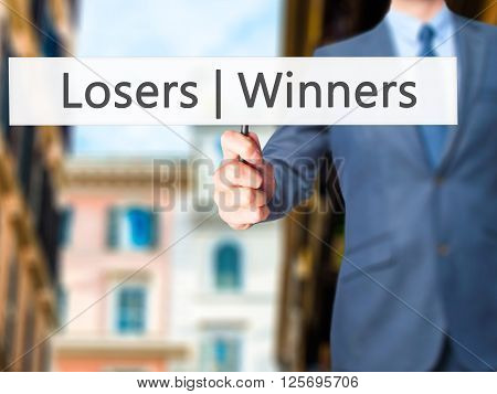 Winners  Losers - Businessman Hand Holding Sign