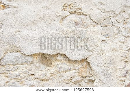 Old beige stone wall background texture close up
