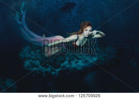 Mermaid Girl floats on the sea floor.