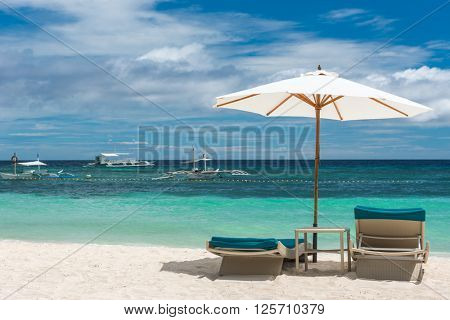 Tropical beach background from Boracay island with Beach chairs on the white sand beach with cloudy blue sky. Travel Vacation