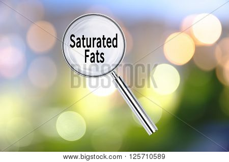 Magnifying lens over background with text Saturated fat, with the blurred lights visible in the background. 3D rendering.