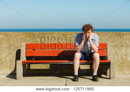 Tired exhausted man sitting on bench by sea ocean. Young guy relaxing outdoor. Summer vacation.