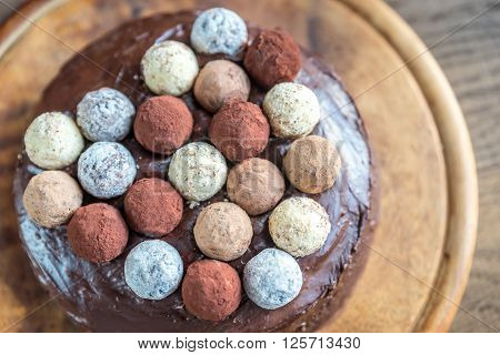 Sacher torte decorated with truffles on the wooden board