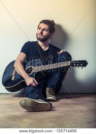 Photo of a young attractive man with long hair and beard sitting on the floor and holding an acoustic guitar. Filtered to look vintage.