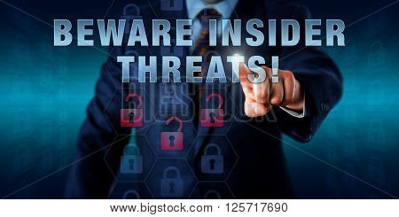 Male white collar worker is pressing BEWARE INSIDER THREATS! on a touch screen. Business challenge metaphor information technology and computer security concept for insider-caused loss of data.