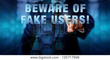 Corporate manager pushing BEWARE OF FAKE USERS! on an interactive screen. Information technology metaphor and computer security concept for criminal infiltration of websites and enterprise networks.