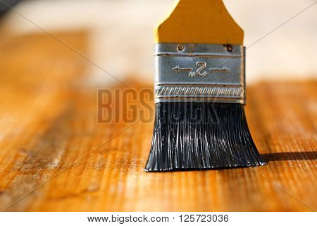 Paintbrush sliding over wooden surface protecting wood for exterior influences weathering insects and fungus. Carpentry woodwork home improvement do-it-yourself concept and background. ** Note: Shallow depth of field