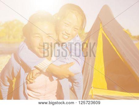 Happy Mongolian girls playing piggyback at campsite.