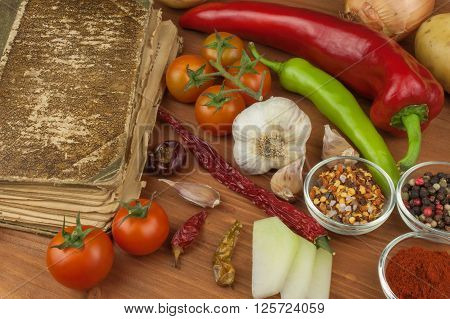 Old cookbook recipes on a wooden table. Cook healthy vegetable. Preparation of home diet food. Different kinds of vegetables.