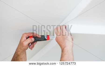 Constructor insulating the ceiling from the interior with polyethilene foam for thermal insulation. poster