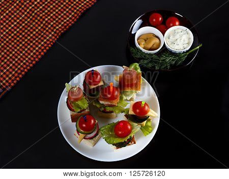 Small snacks canape with cherry tomatoes cheeze sausages and vegetables on bread on skewers on white plate with plate of sauces against black background horizontal overhead view