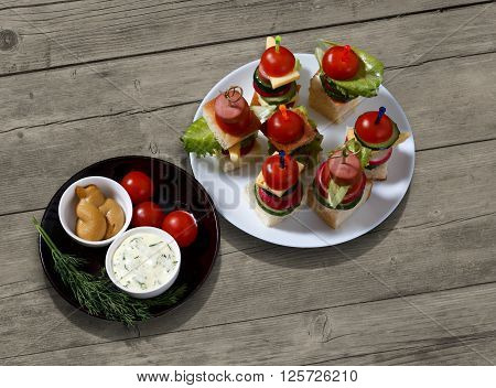 Small snacks canape with cherry tomatoes cheeze sausages and vegetables on bread on skewers on white plate with plate of sauces against rustic wooden background horizontal overhead view