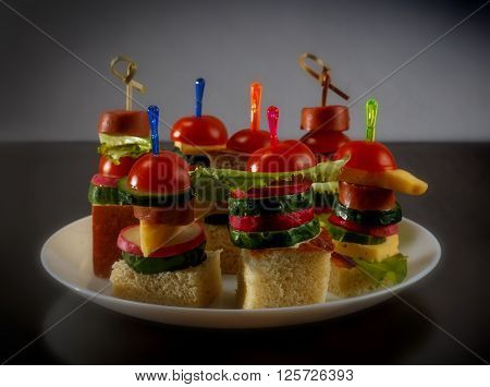 Small snacks canape with cherry tomatoes cheeze sausages and vegetables on bread on skewers on white plate against black background horizontal view