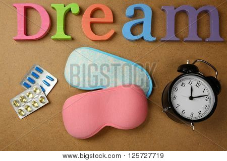Insomnia concept. Sleeping accessories on plywood background