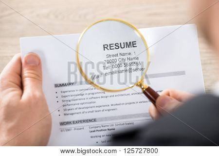 Businessman Analyzing Resume Using Magnifying Glass