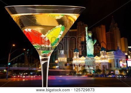 Close-up picture of evening city background with full martini glass with two dibs inside