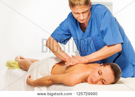 Masseur doing massage on beautiful woman body in the spa salon