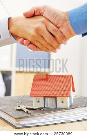 People shake hands over mortage deal for financing a house