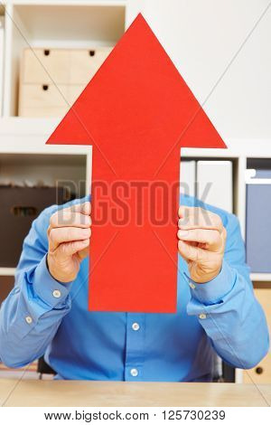 Business man in office holding big red arrow up