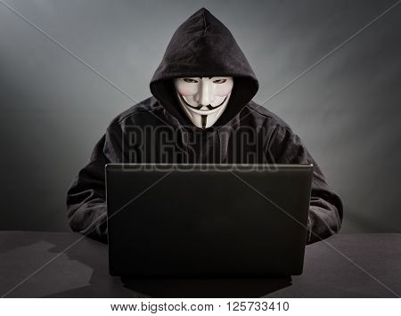 Bełchatow Poland - December 18 2015: Man with the laptop wearing Vendetta mask - symbol for the online hacktivist group Anonymous. Black background.