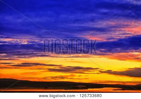 Panoramic view of sunset in fjords.  Blue, purple, orange, yellow coloured sky with stratus clouds. Norway.