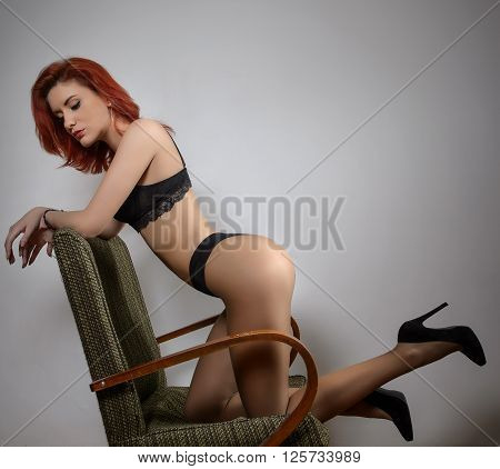 Attractive red hair model with black lingerie sitting provocatively on chair, gray background. Fashion portrait of sensual woman - studio shot. Beautiful redhead female in black posing provocatively.