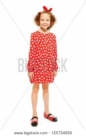 Whole-length portrait of stylish smiling curly-haired girl in red polka-dot dress, isolated on white background