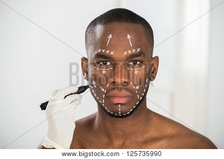 Person's Hand Drawing Correction Lines On Man's Face