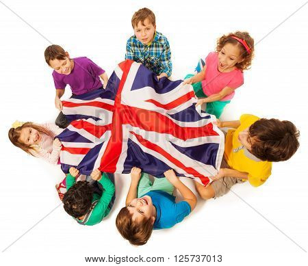 Top view of seven kids holding English flag in the middle of their circle, isolated on white background