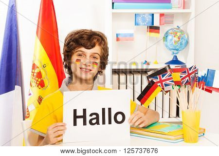 Happy schoolboy with flags on cheeks learning German, holding sign with word Hallo, at the light classroom