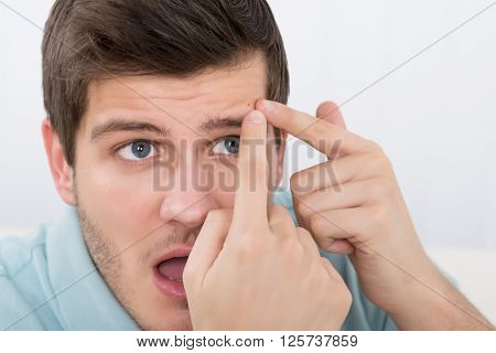 Shocked Young Man Looking At Pimple On Forehead poster