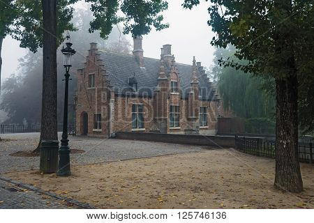Lonely misty autumn morning on the old medieval city park in Bruges Belgium. Ancient brick house and cobblestone pavement with fallen leaves wide angle view.