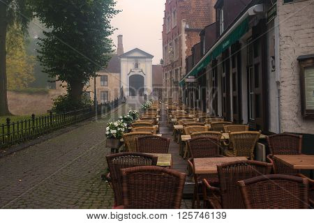 Early autumn morning in Begijnhof Brugge Belgium. Mist over the cobblestone pavement empty restaurant chairs and tables. Abandon and ghost little medieval town concept. poster