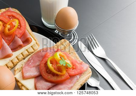 Pork tenderloin sandwiches cheese tomato pepper and parsley in ceramic plates arranged with boiled eggs placed in a metal stand spoon fork knife and glass of milk close up on gray neutral gradient background.