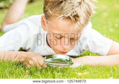 Boy With Magnifying Glass Outside In Grass