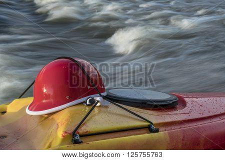 whitewater kayaking helmet on a kayak deck against river rapid