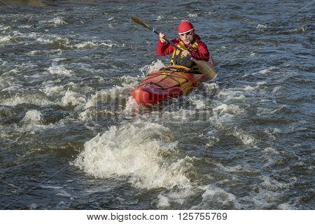 whitewater kayaker paddling upstream the river rapid