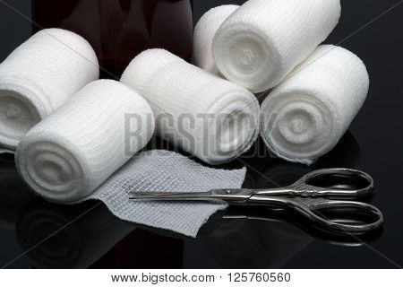 Medical bandage with scissors on black background