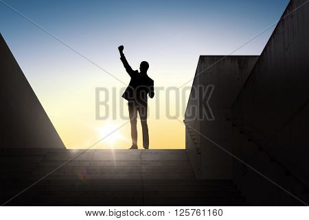 business, success, gesture and people concept - silhouette of happy businessman raising fist and celebrating victory standing on stairs over sun light background