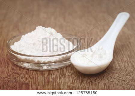 Baking powder in a glass bowl and spoon