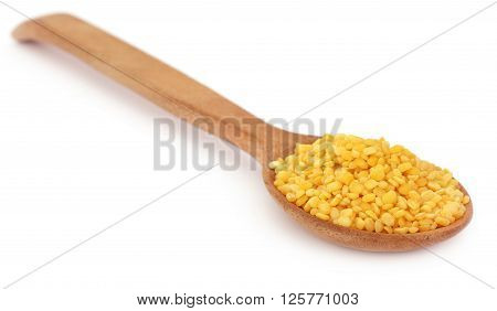 Mung dal in wooden spoon with selective focus