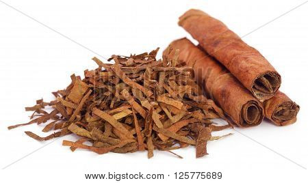 Dry tobacco leaves with cigarette over white background