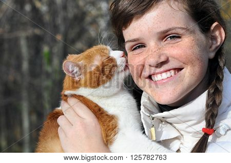 happy freckled girl and funny red cat outdoors