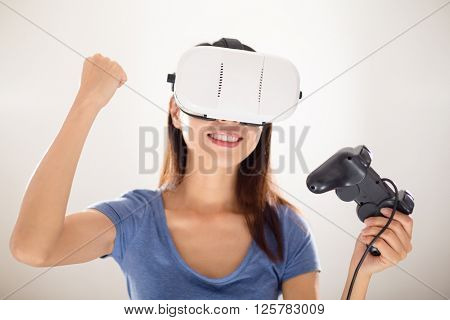 Thrilled Woman play video game with joystiack and VR device poster