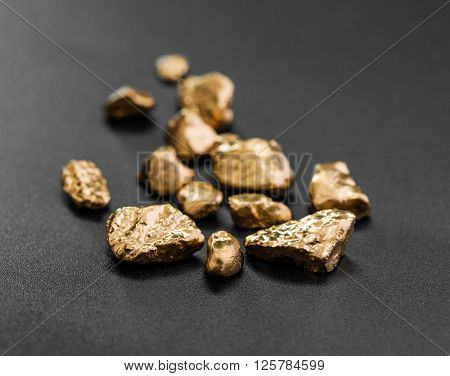 handful of gold nuggets close-up on a black background