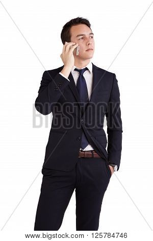 A young caucasian male businessman looking thoughtful holding a mobile phone looking away from camera.