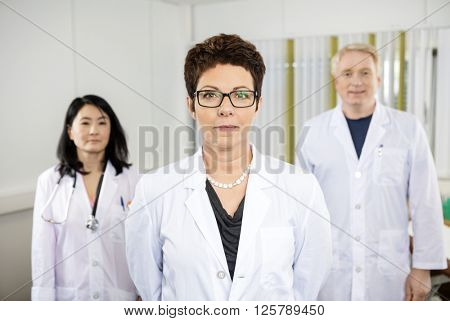 Confident Female Doctor Standing With Colleagues
