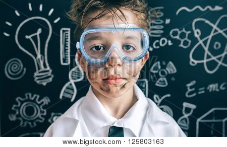 Close up of serious scientist boy with glasses and dirty face looking at camera against of chalkboard with drawings