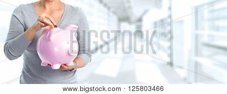 Woman hands with a piggy bank.