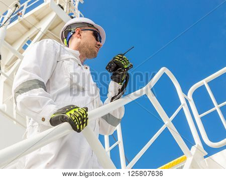 Engineer in white helmet and workwear with VHF under blue sky